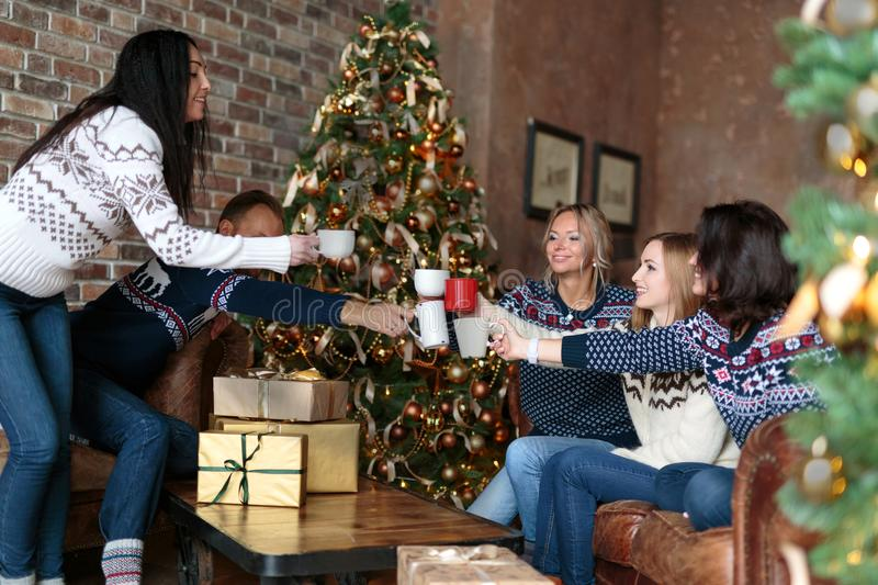 Young people toasting with mulled wine while celebrating Christmas. Near decorated Christmas tree in cozy loft stock image