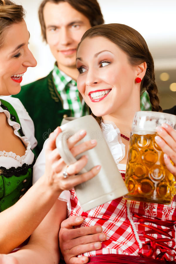 Young People In Traditional Bavarian Tracht In Restaurant Or Pub Stock Photography