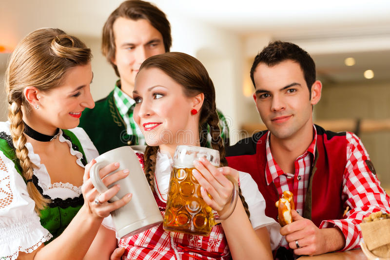 Young People In Traditional Bavarian Tracht In Restaurant Or Pub Stock Photos