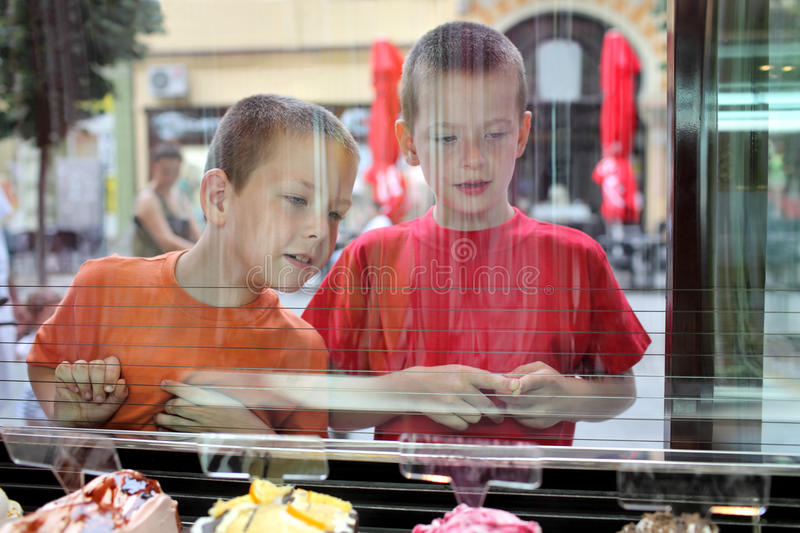 Young people. Two young Caucasian boy looking ice cream in pastry shop, real people royalty free stock images