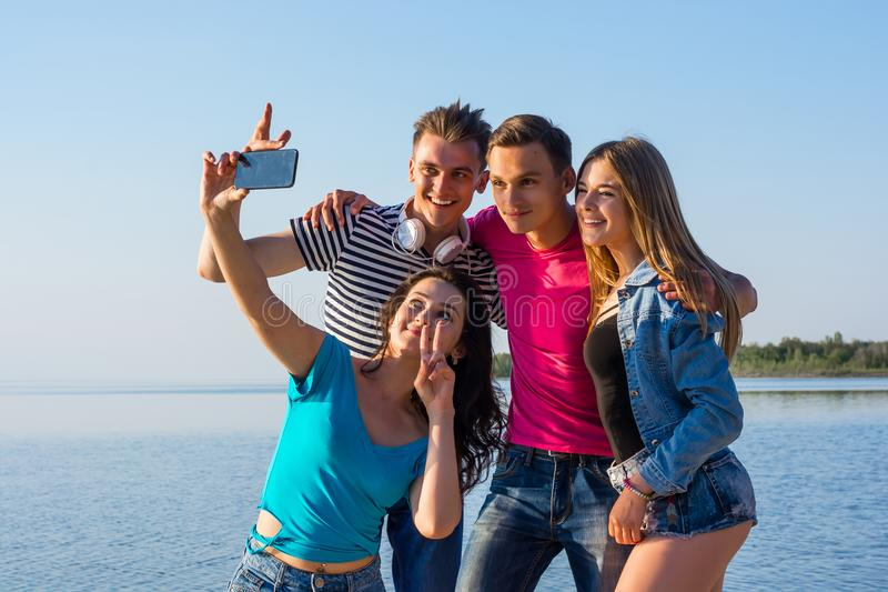 Young people - two guy and two women, brunette and blonde - laugh and do selfie by the seashore stock photo
