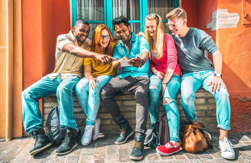 Multiethnic young people using smartphone at school building backyard - Happy friends on addict mood with mobile smart phones stock image
