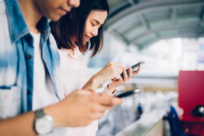 Young people are using smartphone and smiling while sitting on free time. royalty free stock images