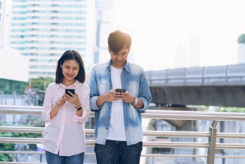 Young people are using smartphone and smiling while sitting on free time. stock photography