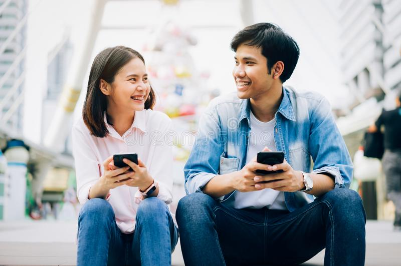Young people are using smartphone and smiling while sitting on free time. stock image