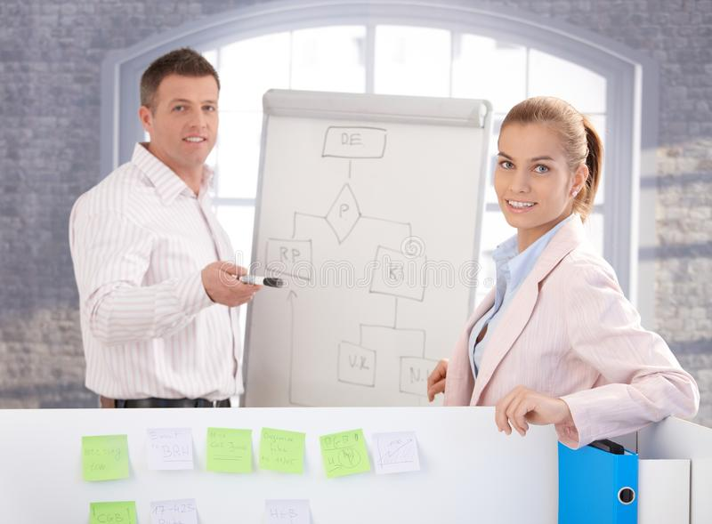 Young people using whiteboard in office smiling