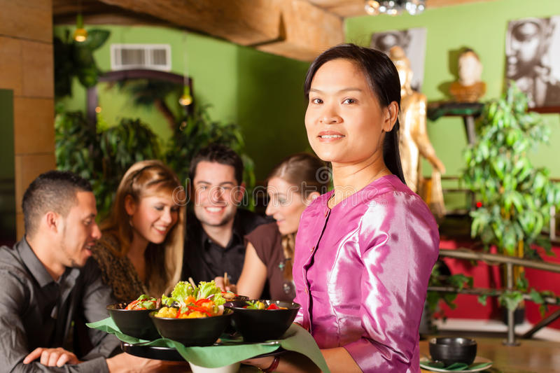 Young people with waitress eating Thai. Young people eating in a Thai restaurant; the waitress brings the dishes, rice and others royalty free stock photos