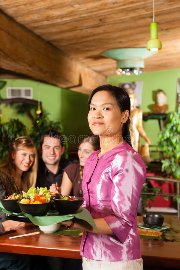 Young people with waitress eating Thai. Young people eating in a Thai restaurant; the waitress brings the dishes, rice and others stock photo