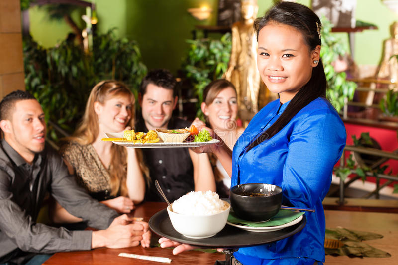 Young people with waitress eating in Thai restaurant. Young people eating in a Thai restaurant; the waitress brings the dishes, rice and others stock image