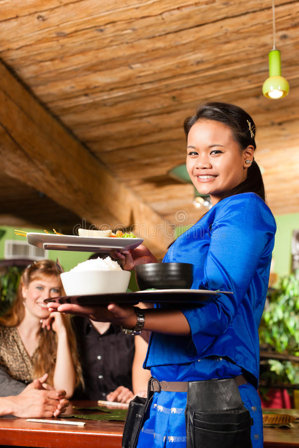 Young people with waitress eating in Thai restaurant. Young people eating in a Thai restaurant; the waitress brings the dishes, rice and others royalty free stock photos
