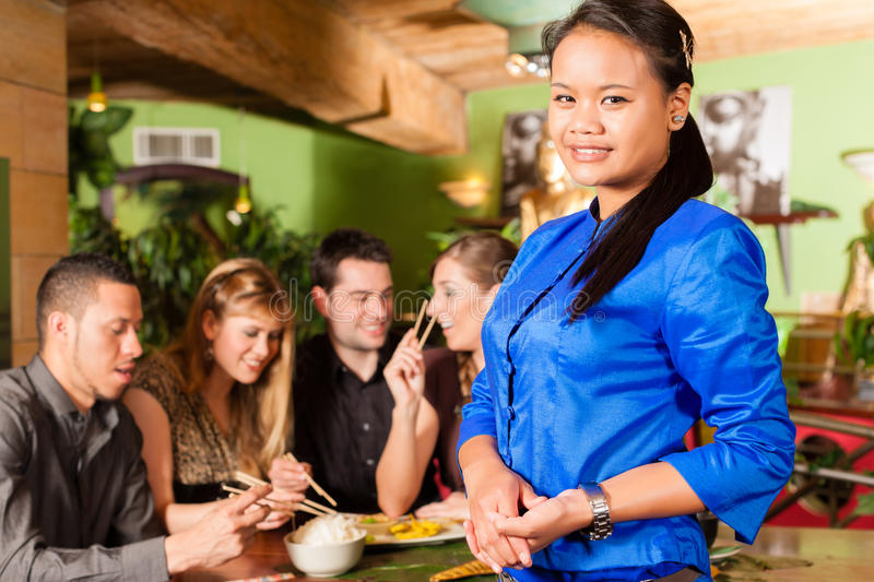 Young people with waitress in Thai restaurant. Young people eating in a Thai restaurant; the waitress brings the dishes, rice and others royalty free stock images