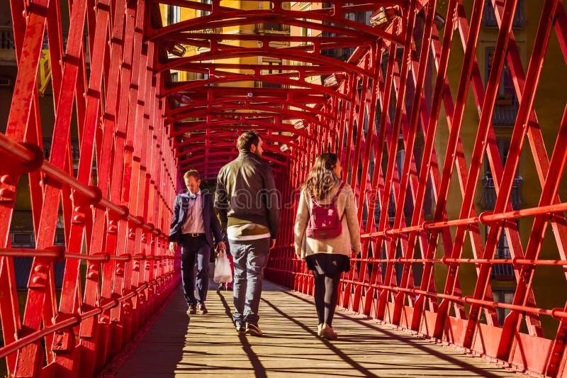 Young people walking on Eiffel Bridge Pont de les Peixateries Velles, a famous pedestrian red steel bridge in Girona stock image