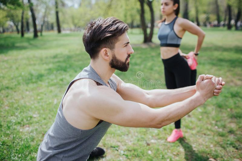 Young people are warming up. He is doing squats while she is stratching her legs behind him. They are wokring separately stock photos