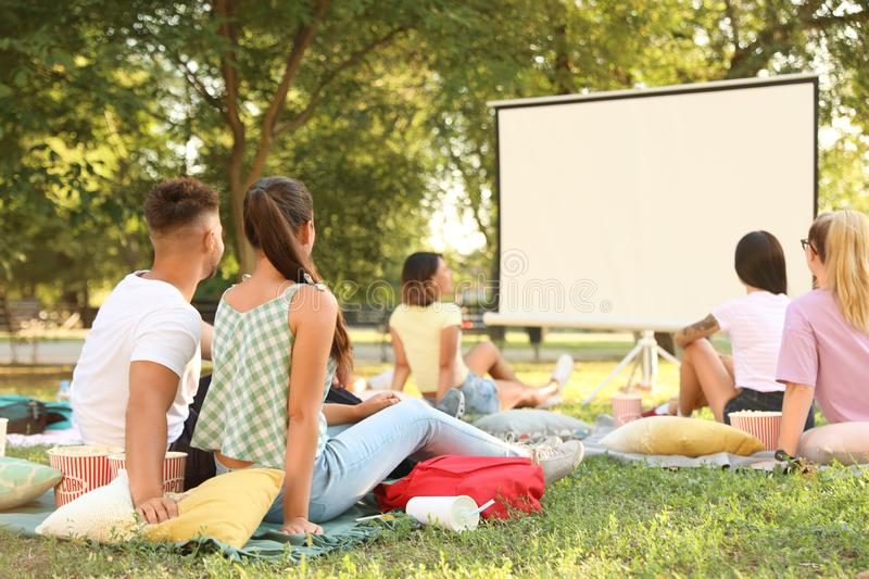 Young people watching movie in open air cinema royalty free stock photo