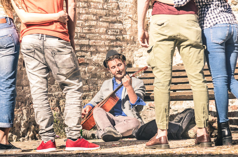 Young people watching street artist performer playing guitar. Young people watching street artist performer playing acoustic classic guitar outdoors - Adventure royalty free stock photo
