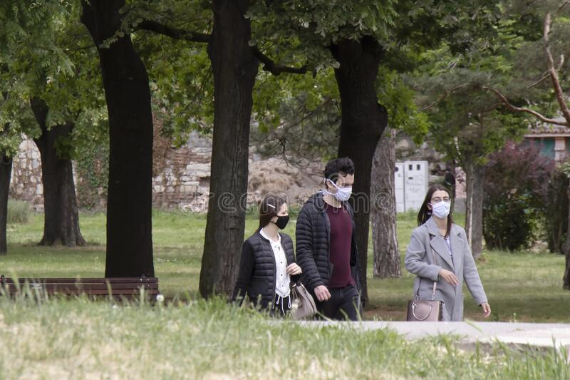Young people wearing face masks while walking in nature, in city public park stock photos