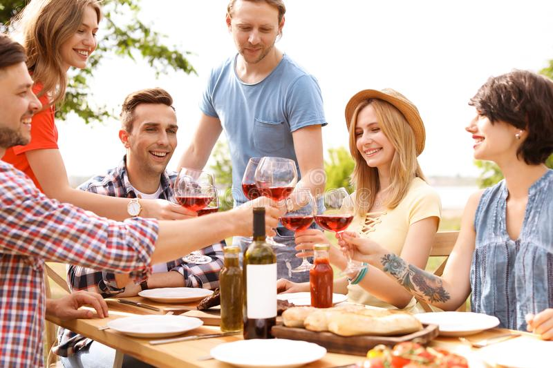 Young people with wine at table outdoors. Summer barbecue. Young people with glasses of wine at table outdoors. Summer barbecue royalty free stock images