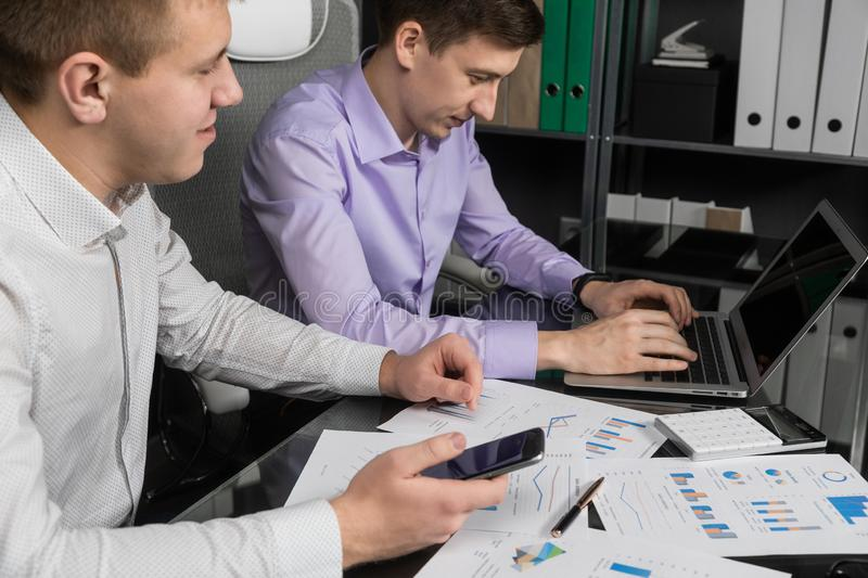 Young people work with a calculator and a phone on the laptop stock photo