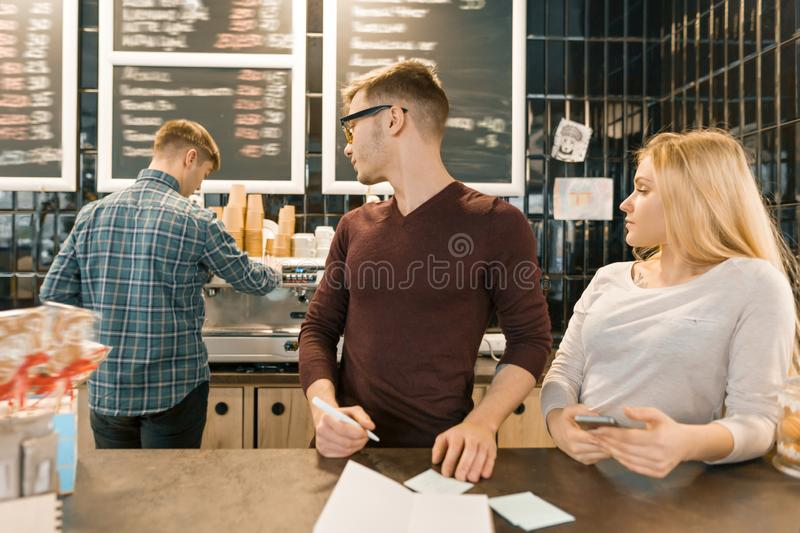 Young people working in coffee shop, man and woman near bar counter, receiving order by phone, barista on the background of coffee stock photography