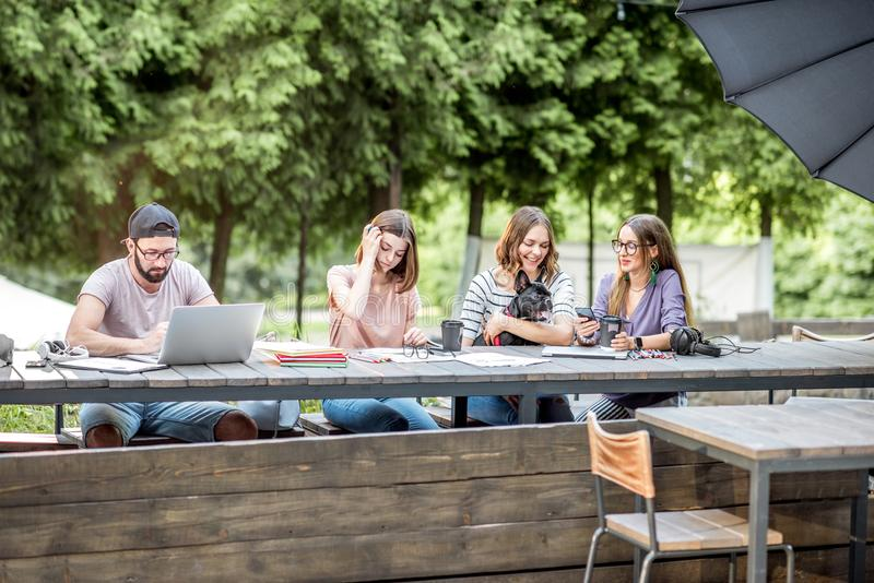 Young people working at the outdoor cafe. Young people sitting at the big table working or studying with laptops and documents outdoors in the park stock photos
