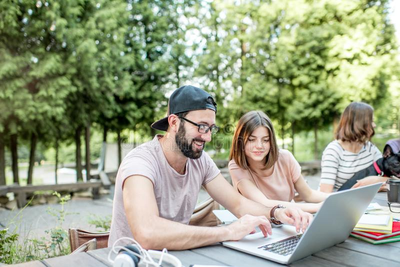 Young people working at the outdoor cafe. Young people sitting at the big table working or studying with laptops and documents outdoors in the park stock images