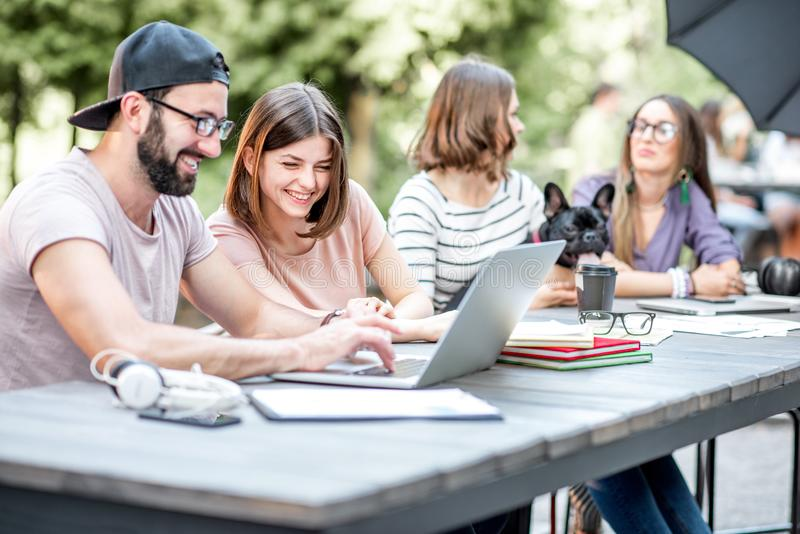 Young people working at the outdoor cafe. Young people sitting at the big table working or studying with laptops and documents outdoors in the park royalty free stock photography