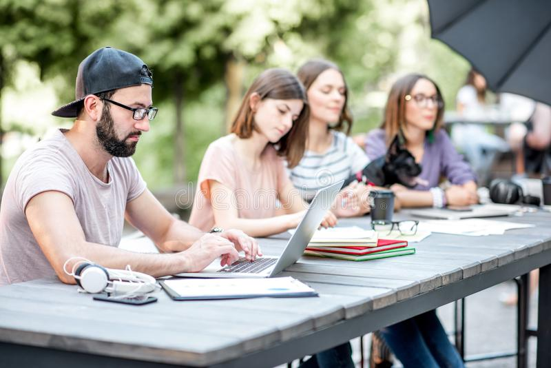 Young people working at the outdoor cafe. Young people sitting at the big table working or studying with laptops and documents outdoors in the park royalty free stock photo
