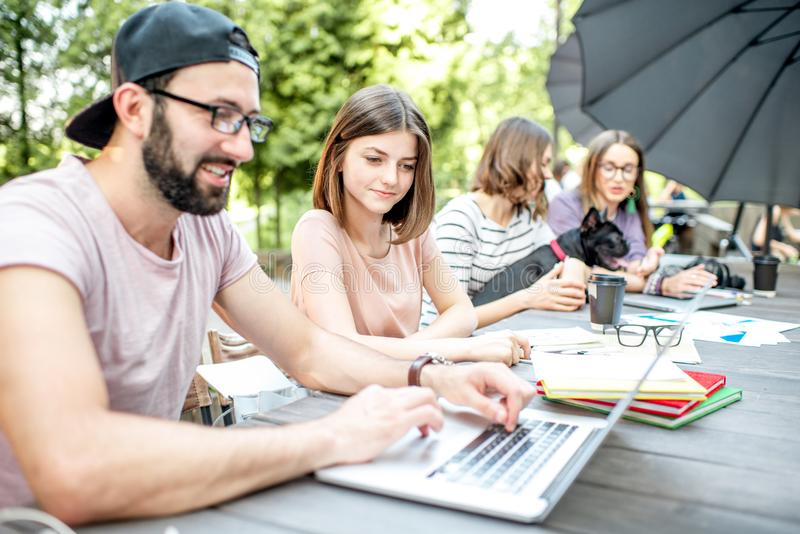 Young people working at the outdoor cafe. Young people sitting at the big table working or studying with laptops and documents outdoors in the park stock photo