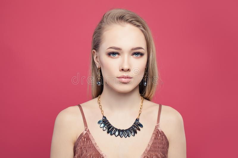 Young perfect blonde woman with gold jewelry chain necklace with hematite stones, fashion portrait on pink background stock photography