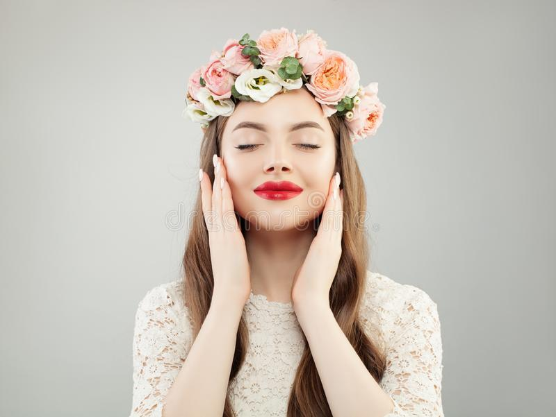 Young Perfect Model Woman Enjoying Spring. Beautiful Girl with Curly Hair, Makeup and Flowers Relaxing royalty free stock images