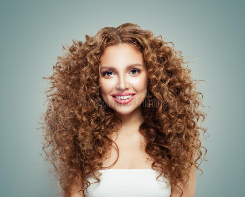 Young perfect redhead woman with long healthy curly hair and cute smile. Beautiful female face stock photo