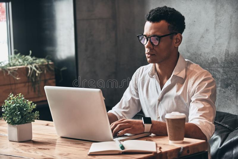 Young perfectionist. Handsome young African man in eyewear worki. Ng using laptop while sitting in the office stock images