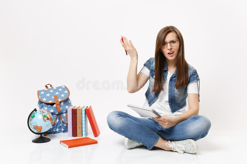Young perplexed woman student in glasses spreading hands holding pencil and notebook sitting near globe backpack books. Young perplexed woman student spreading royalty free stock image