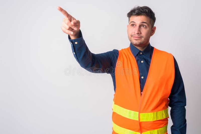 Young Persian man construction worker pointing finger and directing stock image