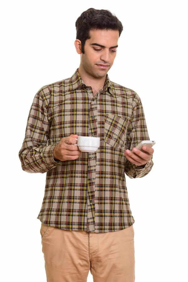 Young Persian man using mobile phone while holding coffee cup royalty free stock photo