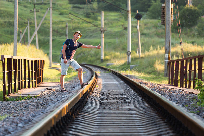 Young Person catching Train on Countryside Railroad Bridge. Young Person catching Train showing hitch-hiking Hand Sign on dirty Countryside Railroad Bridge with royalty free stock images