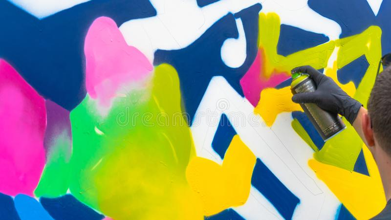 The Young person drawing with sprays - Graffiti artist painting with aerosol color cans on the wall. Street art. Abstract background image of graffiti painting royalty free stock photography