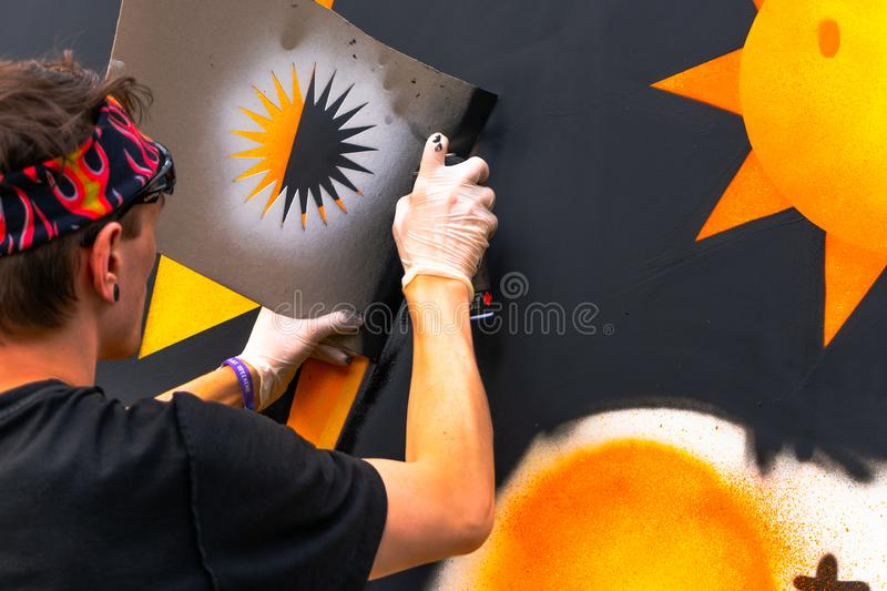 The Young person drawing with sprays - Graffiti artist painting with aerosol color cans on the wall royalty free stock photo