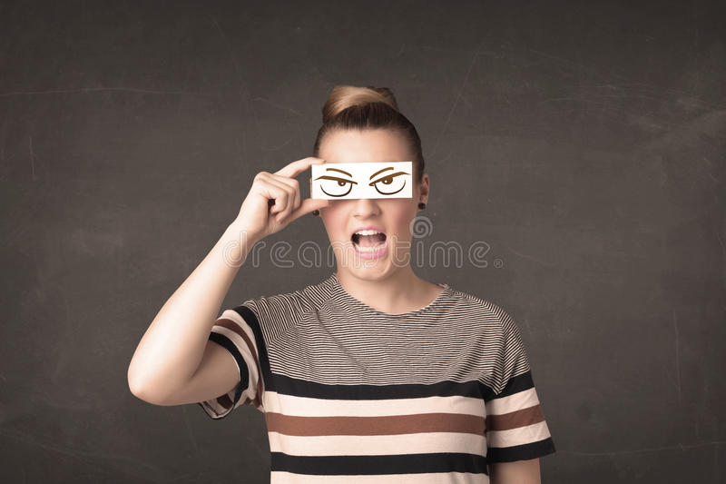 Young person holding paper with angry eye drawing. Concept royalty free stock photography