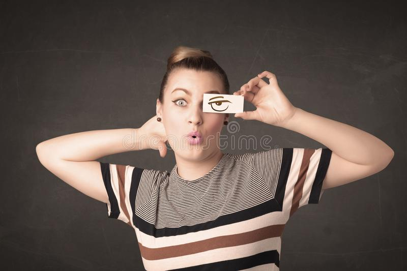 Young person holding paper with angry eye drawing. Concept royalty free stock photo