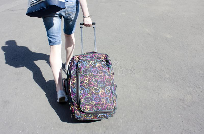 Young person rolling a suitcase, detail royalty free stock photography