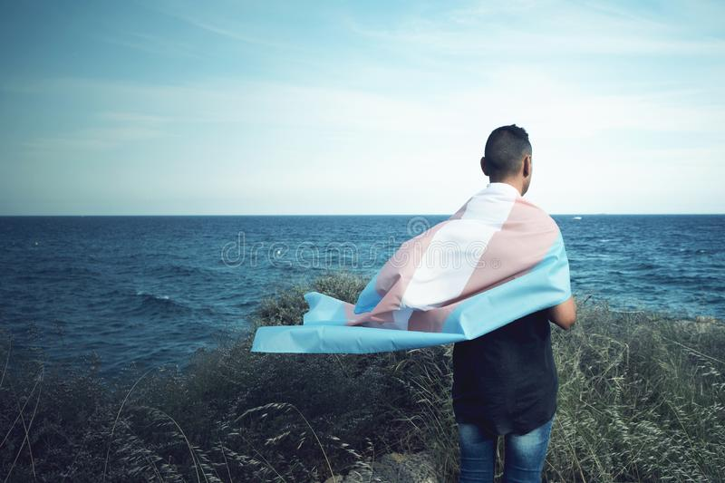 Young person with a transgender pride flag. A young caucasian person, seen from behind, draping a transgender pride flag over his or her shoulders, facing the royalty free stock image