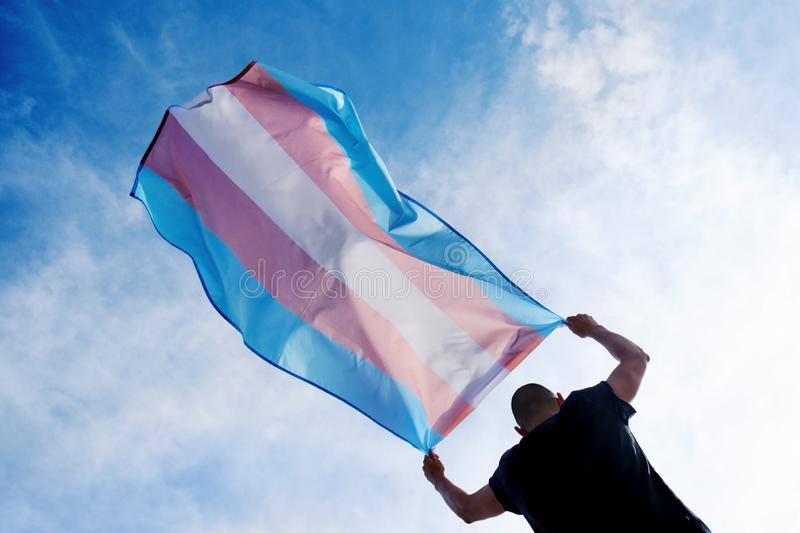 Young person with a transgender pride flag. A young caucasian person, seen from behind, holding a transgender pride flag over his or her head against the blue stock images