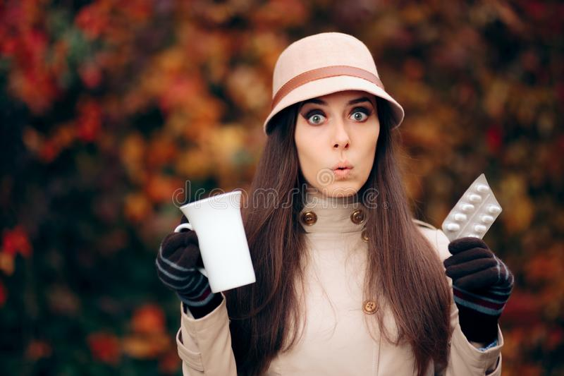 Woman Holding Tea Mug and Pills Treating a Cold in Autumn Season stock photography