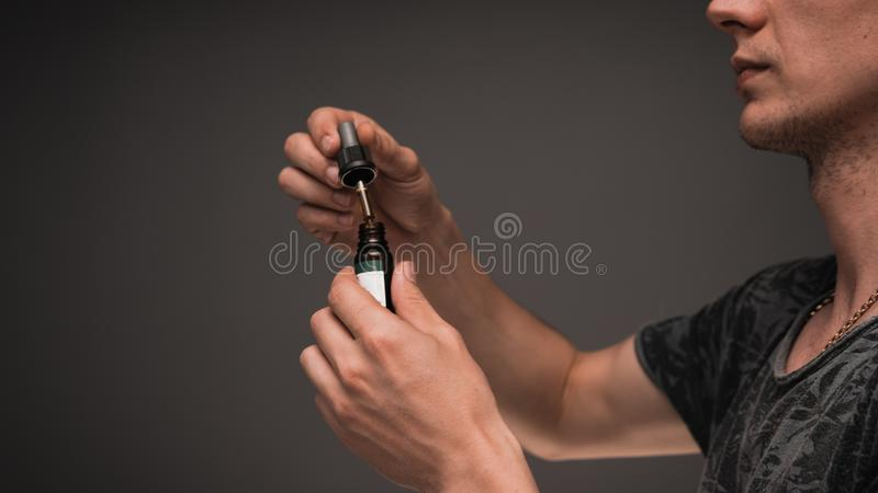 The young person uses hemp oil. Cannabis is a concept of herbal medicine royalty free stock photos