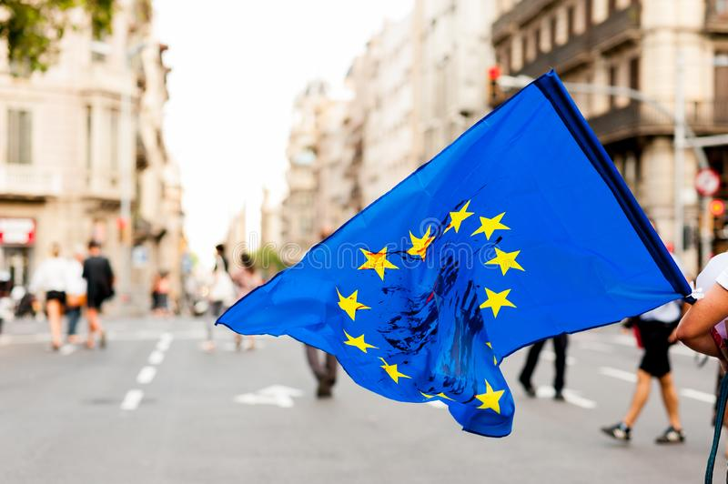 Young person walks in the streets in daylight holding european union flag with blood stains on it protesting against immigration. European union flag with blood stock photos