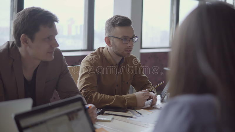 Young and perspective mixed race team discussing new project. Creative group of people working on start-up idea. royalty free stock image