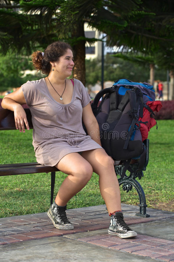 Young Peruvian Woman on Bench with Backpack stock photo