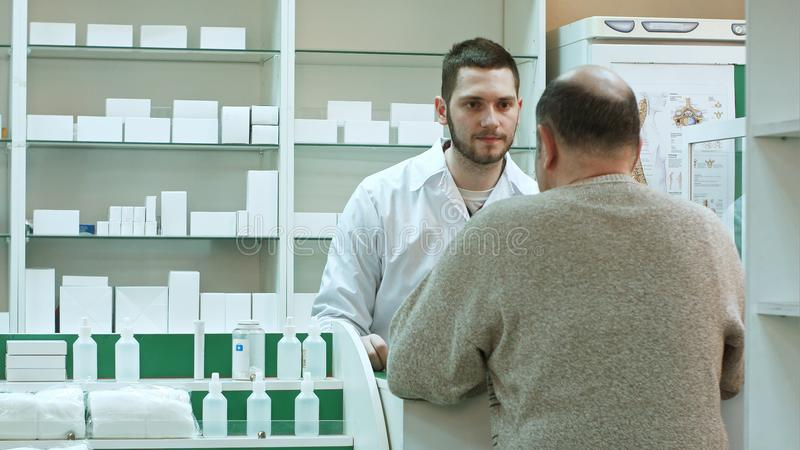 Young pharmacist and senior man customer with drug and prescription at drugstore stock images