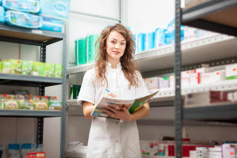 Young pharmacist in the storage facility. Making an inspection. Healthcare business royalty free stock photography